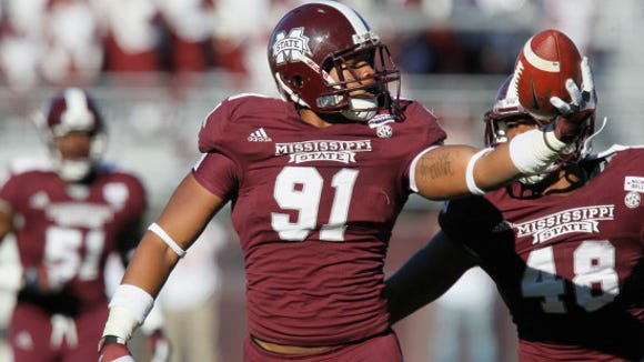 In this Nov 17, 2012 photograph, Mississippi State defensive lineman Preston Smith (91) tosses a recovered fumble to officials in the second half of their NCAA college football game against Arkansas in Starkville, Miss. Mississippi State won 45-14. (AP Photo/Rogelio V. Solis)