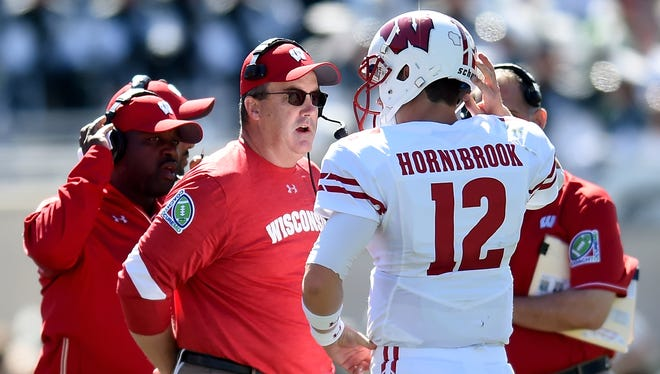 Badger head coach Paul Chryst talks to quarterback Alex Hornibrook during a game against Michigan in 2016.