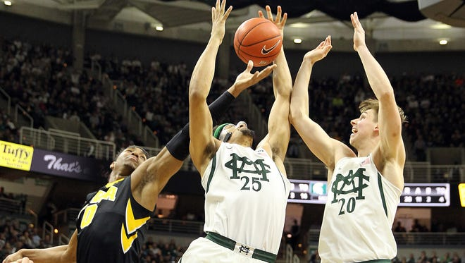 Michigan State's Kenny Goins (25) and Matt McQuaid (20) fight for a rebound against Iowa's Ahmad Wagner during the Spartans' 77-66 win over the Hawkeyes last year in East Lansing.