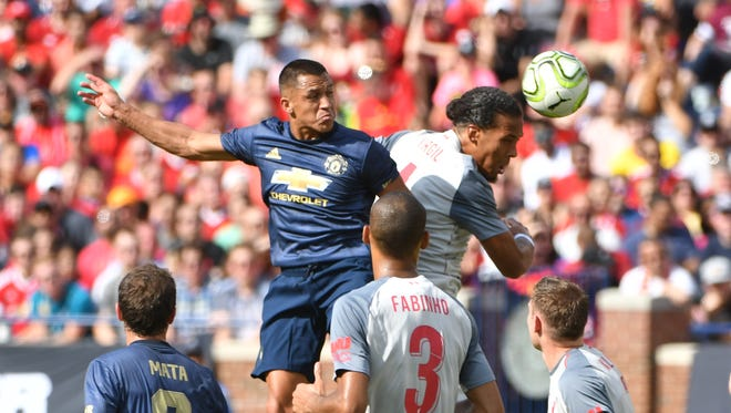 Manchester's Alexis Sanchez and Liverpool's Virgil van Diijk go up for a ball in the first half during Saturday's International Champions Cup match at Michigan Stadium.