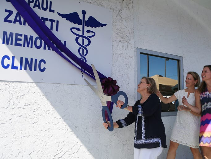 Carole Zanetti (from left) attempts to cut the ribbon