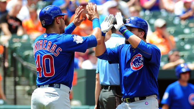 Chicago Cubs designated hitter Kyle Schwarber high fives  Willson Contreras after scoring runs in the second inning against the Baltimore Orioles.