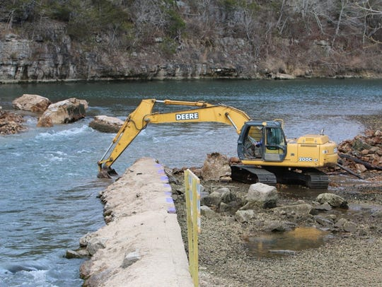 An excavator rips out a section of the Dawt Mill dam