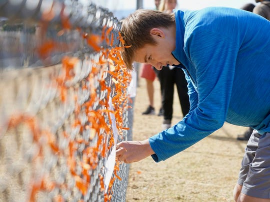 Freshman Andrew Pavicich, 15, ties an orange ribbon onto a fence at Columbine High School in Littleton, Colorado, following a gun-violence walkout on March 14, 2018.