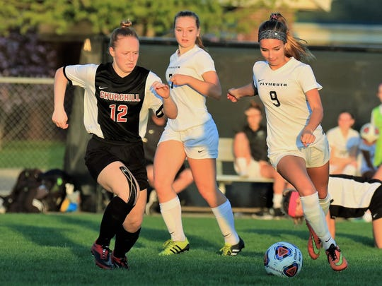 Maneuvering past Livonia Churchill's Loren Kruger (12)