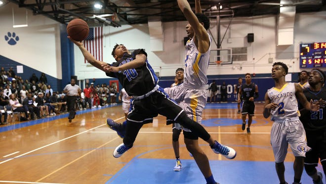 Godby's Tavaris King tries to lay the ball in against Rickards' Marcus Louis during their District 2-6A final at Godby High School on Friday.