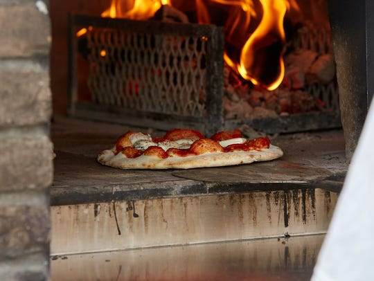 A pizza comes out of the over at Blazin' Woodfired