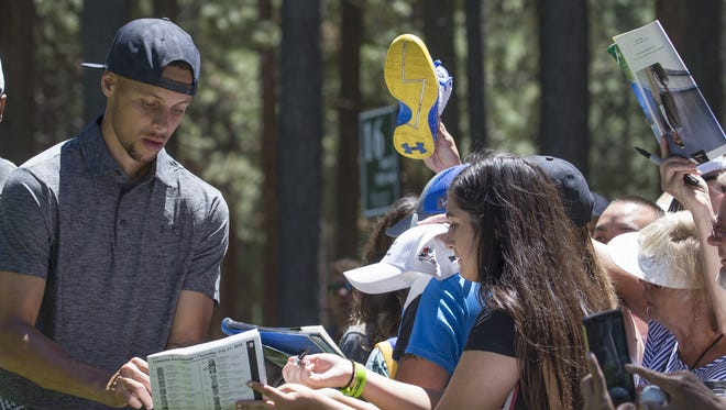 Stephen Curry signs autographs during the ACC golf tournament at Edgewood Golf Course in 2016.