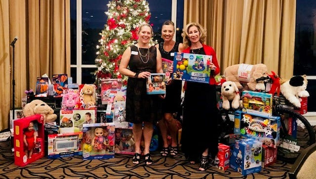 """The """"Santa's Elves"""" co-chairs Ellen Houts and Heidi Monsour and volunteer Brenda Woolston were excited to receive lots of toys and gifts for the Hibiscus children at the Raymond James Annual Toy Drive Party!"""