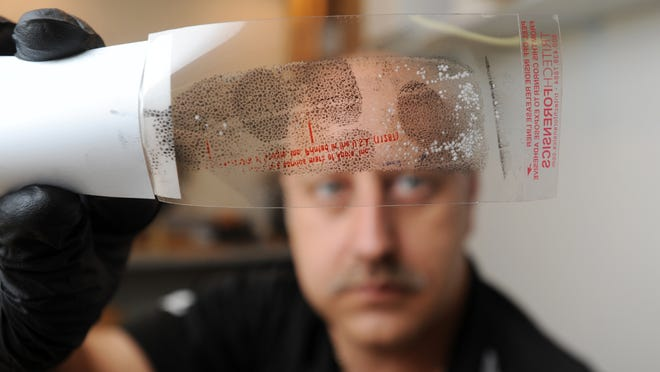 Don Bates, an evidence technician with Zanesville Police Department, looks at fingerprints lifted from a cup. Even with advances with DNA technology, fingerprints are vital clues for solving crimes.
