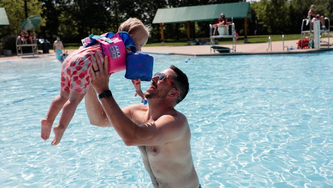 Josh Snyder of Dublin plays with his daughter, Delaney, 2, at the Dublin Community Pool South on Wednesday. Dublin's pools have implemented limited entry, social distancing markers and temperature checks at the entrance.