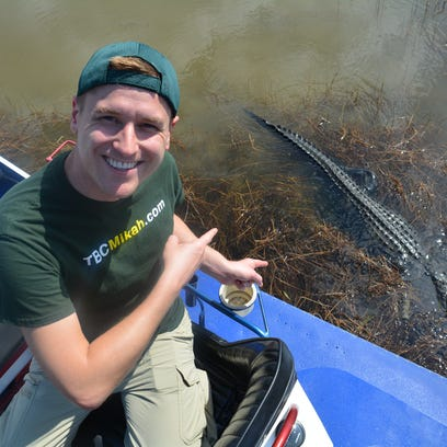 Mikah Meyer poses with an alligator during a trip to