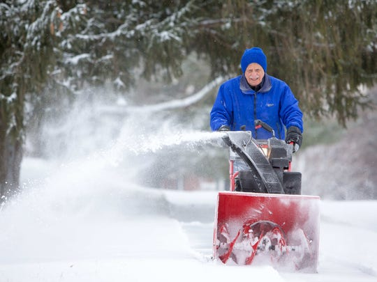 Dan Diguglielmo clears the sidewalk around his home in the Hickory Hill neighborhood of Hockessin as overnight snow brought 1-2 inches to the area.