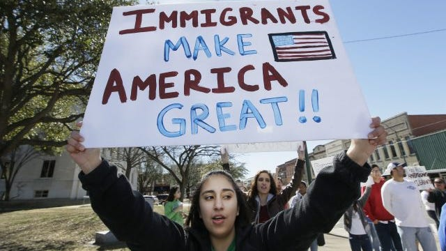 """High school student Kathia Suarez holds up a sign as she protests with others outside the Grayson County courthouse in downtown Sherman, Texas, Thursday, Feb. 16, 2017. In an action called """"A Day Without Immigrants,"""" immigrants across the country are staying home from school and work and closing businesses to show how critical they are to the U.S. economy and way of life."""
