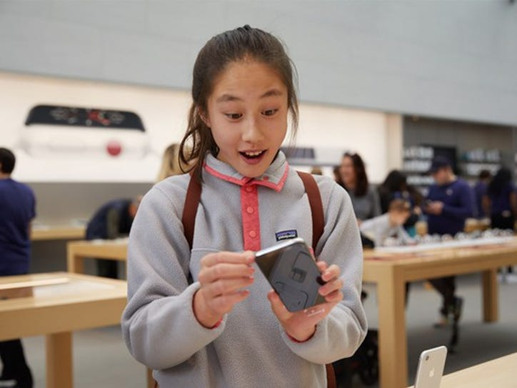 A girl with a surprised expression holds an iPhone in an Apple store.