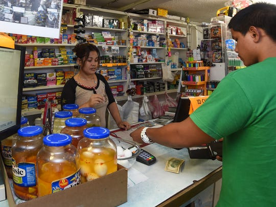 Prices of various goods have increased from a year ago. In this file photo, cashier Nerick Wesen helps a customer at the New Asan Beach Market in Asan on March 8, 2017.