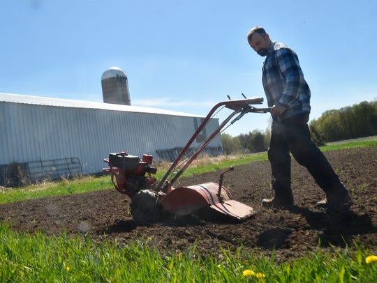 Jake VandenPlas completes the tilling of a large garden
