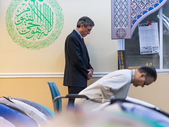 Governor John Carney pays respect during a prayer session
