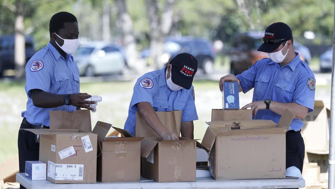 Members of Orange County Fire Rescue on Wednesday pack personal protective equipment items including disposable face masks, reusable masks and hand sanitizer in bags to be handed out to small businesses in Orlando. Coronavirus cases again hit a record Wednesday and have led Daytona Beach's mayor to consider a mask requirement.
