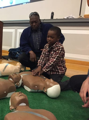 5-year-old Josiah Cartwright learns how to administer hands only CPR while his father supervises during Connect2STEM in Phoenix on Jan. 27, 2018.