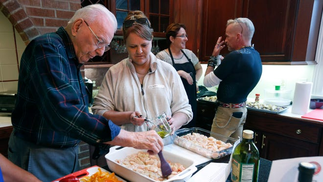 WWII veteran Ralph Edwards, 91, of Pittsford and Army veteran Colleen Bellezza, 47, of Perry help prepare a chicken recipe during a Cooking with Heroes program at the EquiCenter in Honeoye Falls.