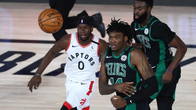 Celtics center Robert Williams III, center, keeps the ball away from Toronto Raptors guard Terence Davis during the first quarter in Game 1 of the second round of the playoffs in Lake Buena Vista, Fla. At right is Celtics swingman Jaylen Brown.