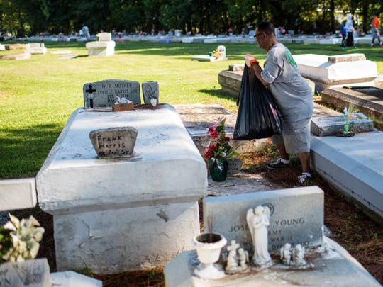 Members of Destiny of Faith Church remove litter from a cemetery on Martin Luther King Jr. Drive in Lafayette, La., Saturday, Sept. 19, 2015.