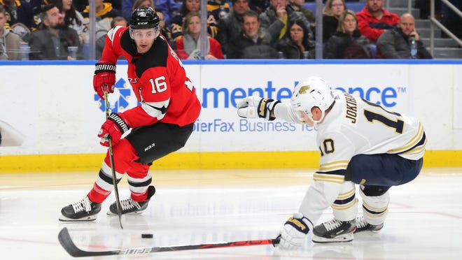Buffalo Sabres defenseman Henri Jokiharju (10) tries to block a pass by New Jersey Devils center Kevin Rooney (16) during the third period at KeyBank Center on Dec. 2, 2019.