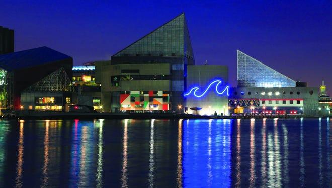 The National Aquarium's iconic facade illuminates Baltimore's skyline.