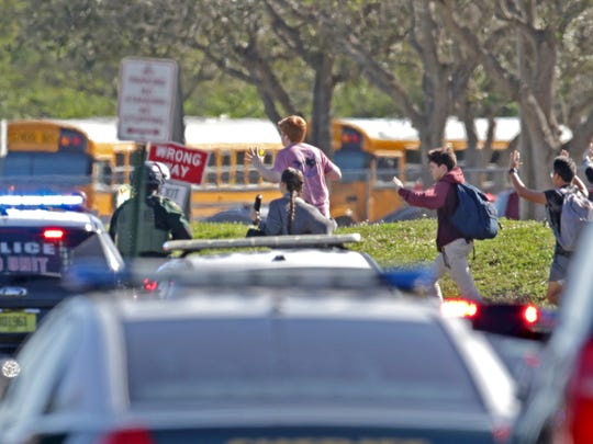 FILE - In this Wednesday, Feb. 14, 2018 file photo, students run with their hands in the air following a shooting at Marjory Stoneman Douglas High School in Parkland, Fla. It was the final period of the day at Marjory Stoneman Douglas High and Jonathan Blank was in history class, learning about the Holocaust. Across campus five of his friends, pals since grade school, sat in different classrooms watching the clock, when a former student opened fire at the school, killing more than a dozen people and injuring others Wednesday afternoon. (John McCall/South Florida Sun-Sentinel via AP, File)