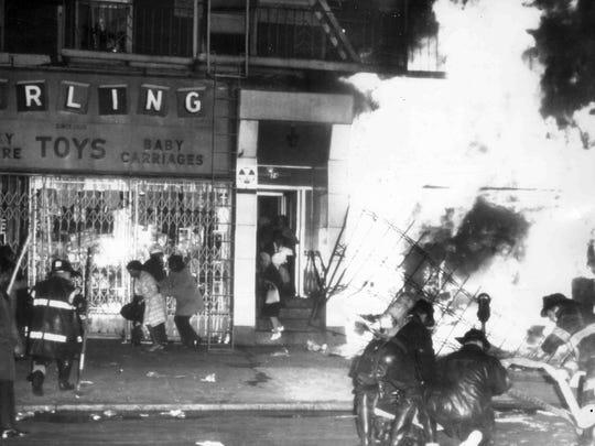 Firemen battle a blaze on 125th Street in Harlem, New