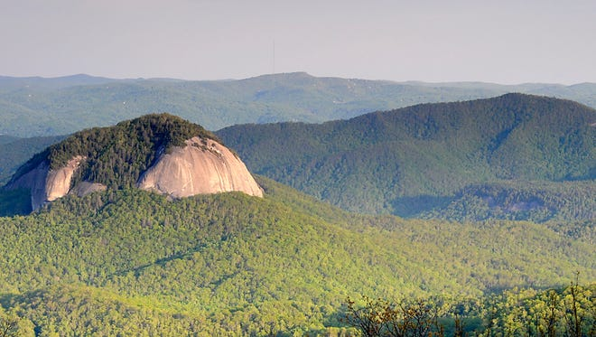 Late afterrnoon sun highlights the rock faces of Looking Glass Rock seen from the Log Hollow Overlook on the Blue Ridge Parkway.