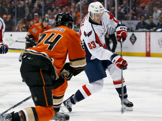 Washington Capitals center Jay Beagle (83) takes a shot on goal as Anaheim Ducks' Simon Despres looks on in the first period of an NHL hockey game in Anaheim, Calif., Monday, March 7, 2016. (AP Photo/Christine Cotter)