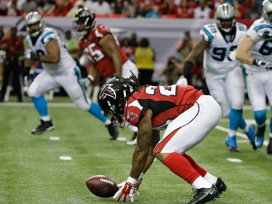 File- This Dec. 27, 2017, file photo shows Atlanta Falcons running back Devonta Freeman (24) fumbling the ball on a run against the Carolina Panthers during the first half of an NFL football game, in Atlanta. Mistakes, including costly fumbles by Devonta Freeman in last week's loss at New Orleans, red zone woes and third-down problems have hurt the Atlanta Falcons all season and left the team needing a win over Carolina on Sunday to guarantee a playoff spot. (AP Photo/David Goldman, File)