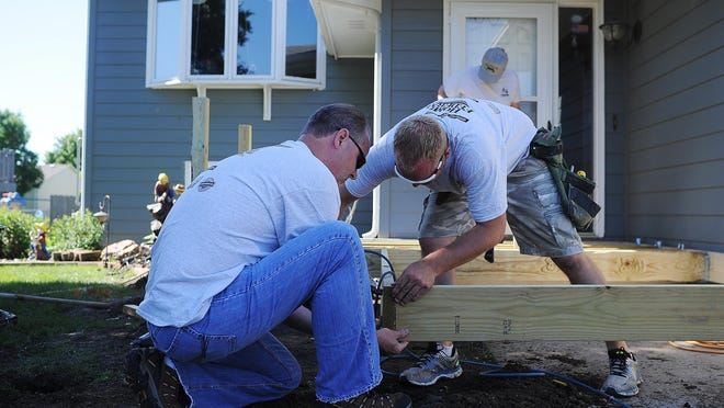 Volunteers Eric Anderson, left, from Home Federal Bank, and Landon Greenfield, from Greenfield Builders, work on a deck with a ramp at Ron and Onalea Barber's home during the Home Builders Association of the Sioux Empire's 22nd annual Repair Affair Day on Tuesday, June 9, 2015, in Sioux Falls. More than 60 volunteers made repairs to six different homes Tuesday throughout Sioux Falls.