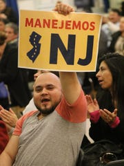 "Yony Dubon, an undocumented person from Guatemala, living in New Jersey holds up a sign that translates to ""Lets Drive NJ"" in Elizabeth."