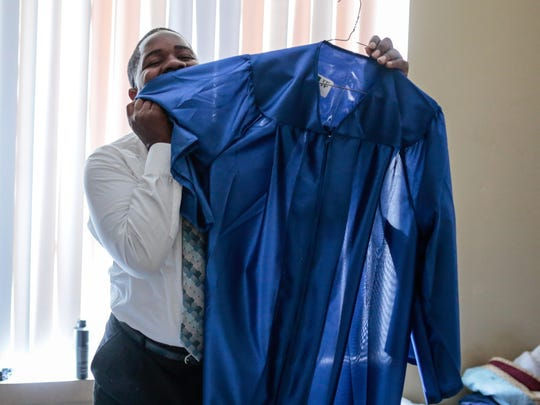 """""""It smells like success,"""" Joshua Sims, 21, said while showing off his robe for graduation as he gets ready to go to prom at Covenant House Michigan in Detroit on Thursday June 8, 2017."""