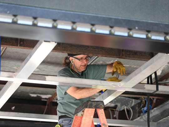 Denis Contant, owner operator of Fab Weld Corporation in Rochester, works on installing the drop ceiling base on the underside of the new marquee as installation of the new signage wraps up at the Little Theatre on East Ave in Rochester Friday, June 9, 2017.