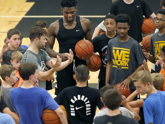 Tyler Relph, left, talks with players during a basketball
