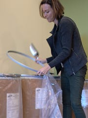 Bree Cox scoops pet food into a bag at Pet Wants GVL. The store recently opened off Woodruff Road.