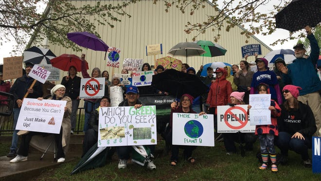 Demonstrators marching in celebration of Earth Day pose for a photo after arriving at the Gypsy Hill Gym in Staunton, Va., on Saturday, April 22, 2017.