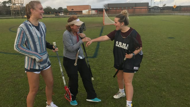 Gulf Breeze lacrosse players Clarke Haas (left), KateRaegan Costello (right) and head coach Carlee Costello are ready to take an already dominant program one step further this year.