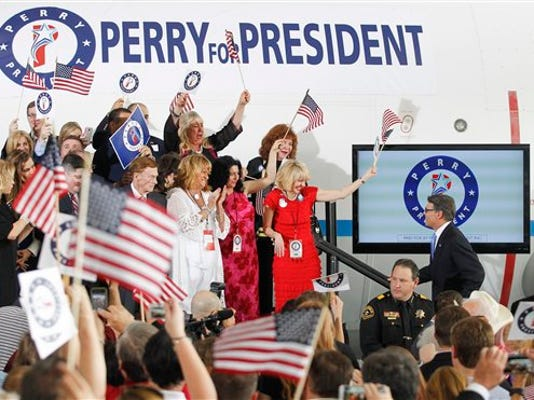 Former Texas Gov. Rick Perry walks on the stage amid supporters prior to announcing the launch of his presidential campaign for the 2016 elections in Addison,Texas, on Thursday, June 4, 2015. (AP Photo/Tim Sharp)