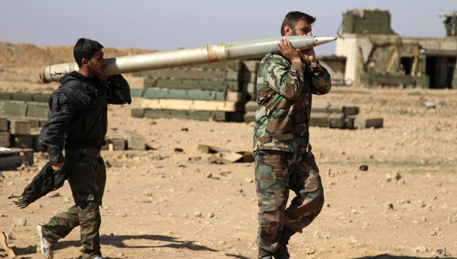 In this file photo of Feb. 17, 2016, soldiers from the Syrian army carry a rocket to fire at Islamic State group positions in the province of Raqqa, Syria.