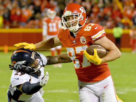Chiefs tight end Travis Kelce (87) stiff-arms his way past Broncos safety Bradley Roby (29) during the second half.