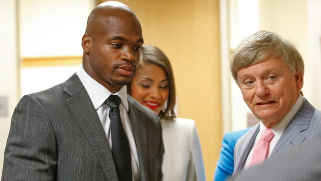 In this Oct. 8 file photo, Adrian Peterson (left) and his attorney Rusty Hardin (right) speak in the Montgomery County Courthouse in Conroe, Texas, before Peterson's arraignment.