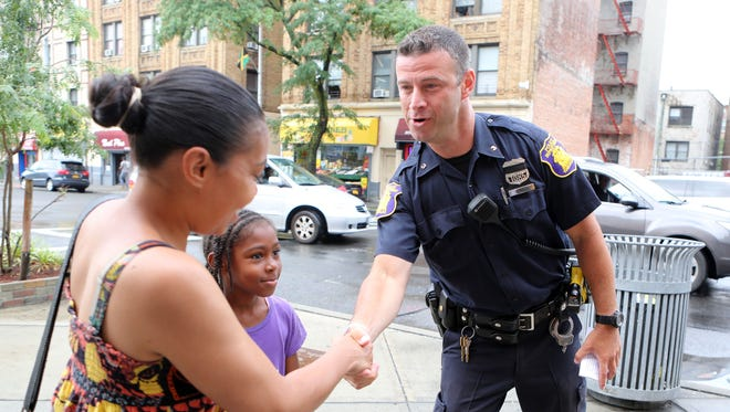 Police officer David Graham greets Liza Mcgilvery and Isis, 8, with a handshake on the corner of Broadway and McLean Avenue in Yonkers, July 29, 2016. Members of the Yonkers Police Department participated in their Stop and Shake campaign, which brings officers onto the streets to shake hands and connect with the community.