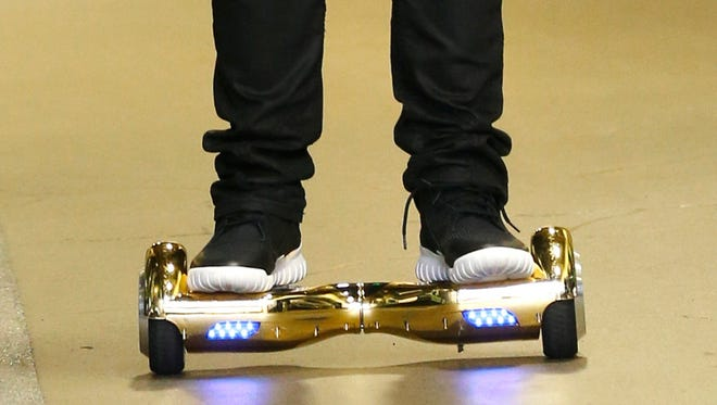 """Seattle Seahawks wide receiver B.J. Daniels rides an electric self-balancing scooter commonly called a """"hoverboard,"""" as he arrives for an NFL football game against the Carolina Panthers, Sunday, Oct. 18, 2015, in Seattle. (AP Photo/Stephen Brashear)"""