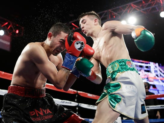 Michael Conlan, of Ireland, punches Tim Ibarra during the third round of a super bantamweight boxing match Friday, March 17, 2017, in New York. Conlan stopped Ibarra in the third round. (AP Photo/Frank Franklin II)