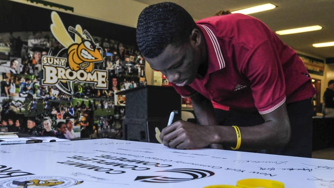 John Roosevelt Hyppolite signs a board at the Student Union at SUNY Broome in 2013 pledging that he will finish his college degree.